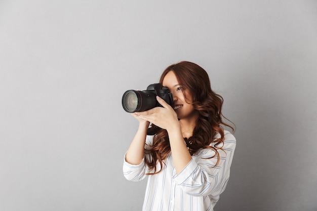 孤立して立っている陽気なアジアの女性、写真カメラで写真を撮る