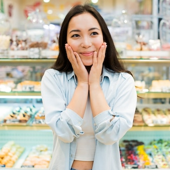 Cheerful asian woman standing with hands on cheeks in bakery store