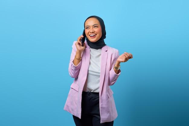 파란 배경 위에 휴대폰으로 친구와 이야기하는 쾌활한 아시아 여성