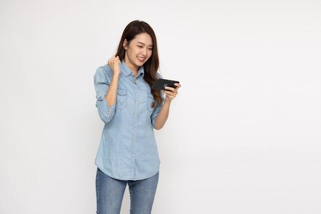 Веселая азиатская женщина с помощью смартфона и получение хороших новостей из сообщения в приложении мобильного чата на белом фоне