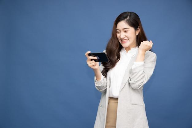 깊고 푸른 표면에 스마트 폰을 사용하는 쾌활 한 아시아 여자.