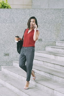 Cheerful asian woman walking down stairs outdoors and talking on mobile phone
