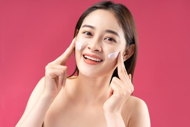 Cheerful asian woman with beautiful skin using lotion