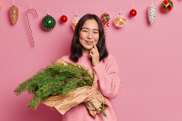 Cheerful asian woman with rouge cheeks smiles gently keeps finger near lips holds bouquet made of evergreen fir tree prepares for holiday celebration enjoys time at home. merry christmas concept