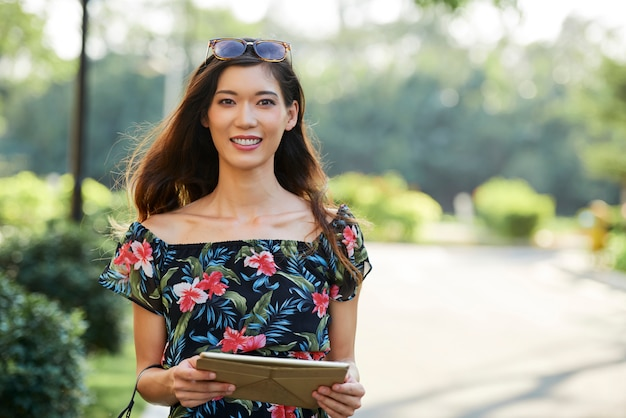 Cheerful asian woman with tablet