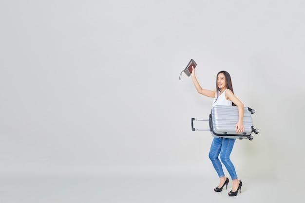 Веселая азиатская женщина с чемоданом путешествия