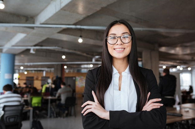 Cheerful asian young businesswoman standing with hands folded in office
