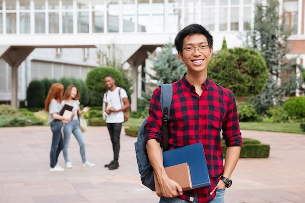 屋外のキャンパスに立っている眼鏡の陽気なアジアの若い男の学生