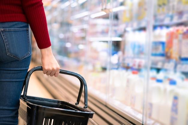 슈퍼마켓에서 쇼핑 바구니를 들고 쾌활 한 아시아 젊은 여자