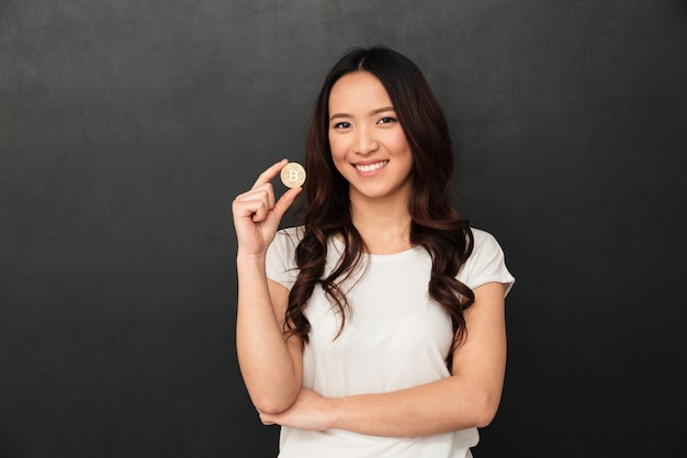 Cheerful asian young woman holding bitcoin looking camera.