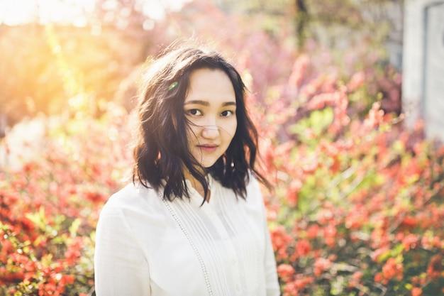 咲く公園で白いブラウスで陽気なアジアの若い女性。