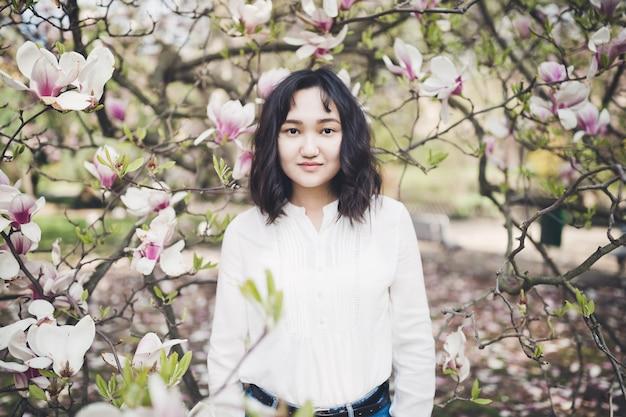 モクレン咲く木の下で白いブラウスで陽気なアジアの若い女性。