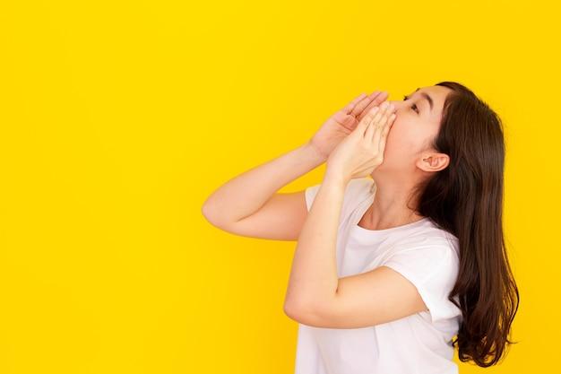陽気なアジアの若い女性が叫んでいる-スタジオの黄色の背景に手をクローズアップで叫んでいます。叫びながら彼女のマウントで手を使用して、女性が大声で話す幸せな美しい少女。広告のコンセプト。