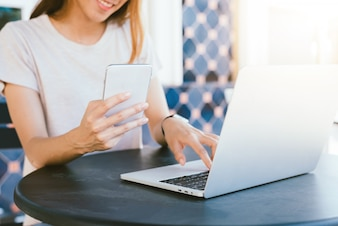 Cheerful asian young woman sitting in cafe drinking coffee and using smartphone for talking
