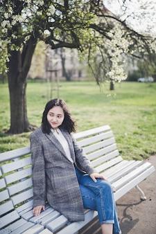 公園の咲く木の下のベンチに座っている陽気なアジアの若い女性