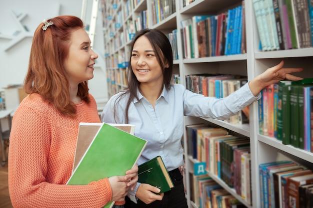 書店で買い物をしながら彼女の友人と話している陽気なアジアの若い女性