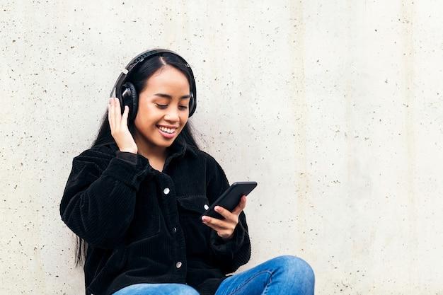 야외에서 콘크리트 벽에 기대어 스케이트보드에 앉아 헤드폰을 끼고 음악을 듣는 쾌활한 아시아 젊은 여성