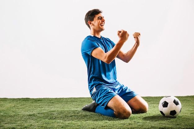 Веселый спортсмен празднует победу на поле