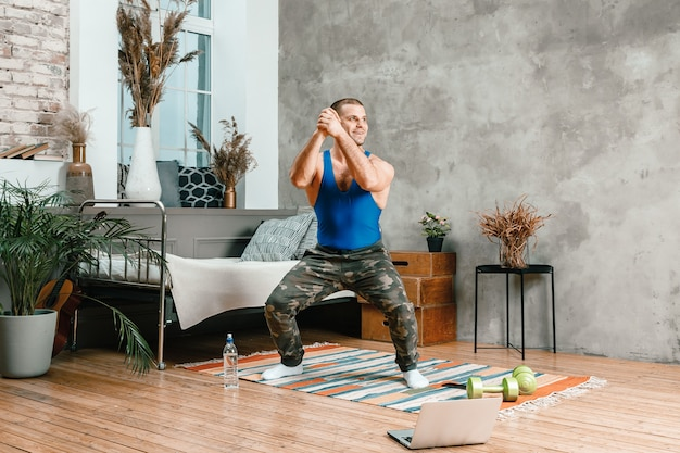 A cheerful athlete with black  hair makes squat  in the bedroom,  online training