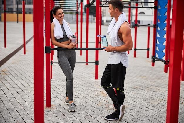 都心の運動場で水を飲みながら元気なアスリート男女がコミュニケーション