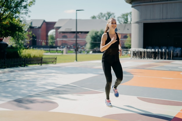 Cheerful athletic woman runs actively on stadium dressed in black sportclothes enjoys physical activities outdoors during summer day being full of energy. people sport and motivation concept