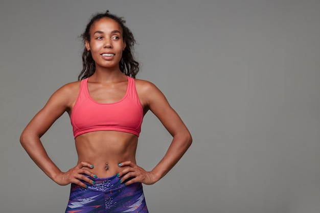 Cheerful athletic young curly brunette lady with dark skin being in good physical shape while standing. sport and healthy lifestyle concept