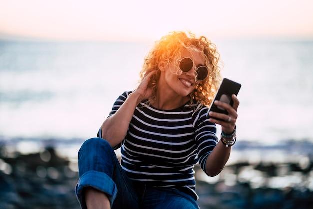 背景に夕日を背景に屋外のモバイルモダンな携帯電話を使用して陽気な魅力的な大人の若い白人女性-人々と技術の屋外レジャー活動-焦点がぼけた海の自然と地平線