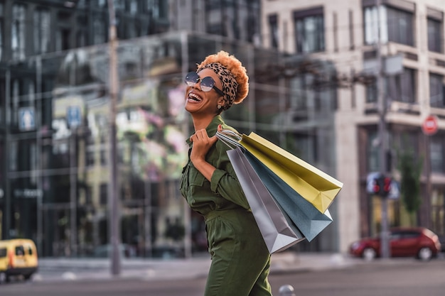 Cheerful attractive afro american lady walking outdoors while holding shopping bags and laughing