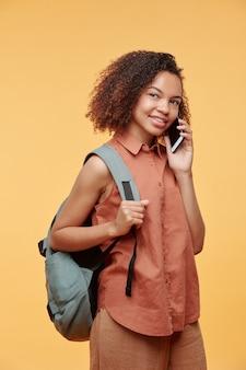 ランドセルを保持し、黄色の背景に電話で学校の友人を呼び出すカジュアルなシャツを着た陽気な魅力的なアフリカ系アメリカ人の学生の女の子