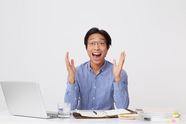 眼鏡をかけた陽気な魅力的なアジアの青年実業家は、手を上げて叫び続け、白い壁の上のラップトップでテーブルに座って興奮しているように見えます
