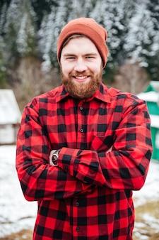 冬の村で手を組んで立っている陽気な魅力的なひげを生やした男