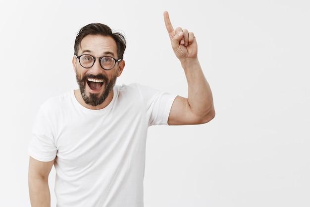 Веселый привлекательный бородатый зрелый мужчина в очках позирует