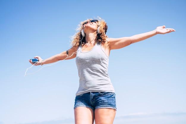 스마트 폰으로 음악을 듣는 동안 열 대 장소에서 해변에서 웃 고 쾌활 한 매력적인 아름 다운 백인 중 년 여자. 휴가를 즐기고 직장에서 자유를 누리는 사람들