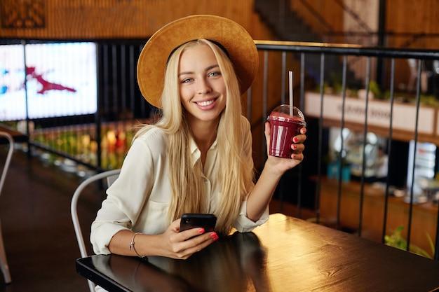 モダンなカフェのインテリアの上に座って、魅力的な笑顔で見て、彼女の手にベリーの飲み物を保ちながら、流行の服を着ている陽気な魅力的な青い目の若いブロンドの女性