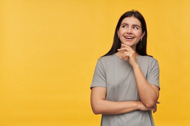 Cheerful attractive brunette young woman in gray tshirt keeps hands folded smiling and looking away to the side at copyspace over yellow wall