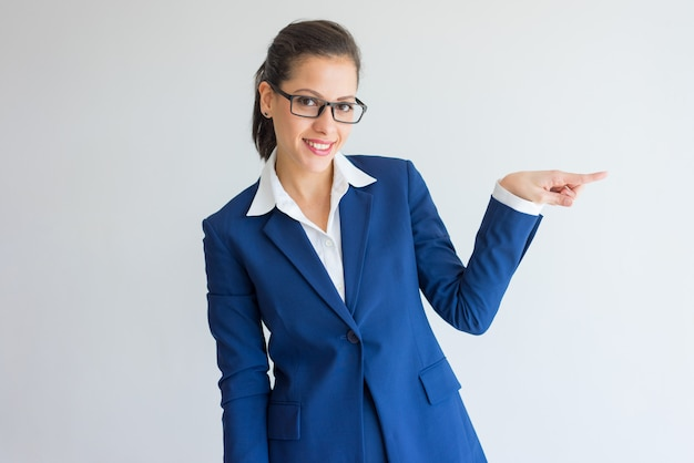Cheerful attractive business lady pointing aside and looking at camera.