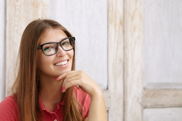 Веселая привлекательная кавказская девушка в прямоугольных очках позирует в помещении у деревянной стены с копией пространства для вашего текста или рекламного контента, взявшись за подбородок и улыбаясь