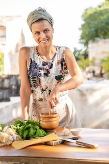 Cheerful attractive caucasian woman in apron chopping basil in garden kitchen. dinner at home concept