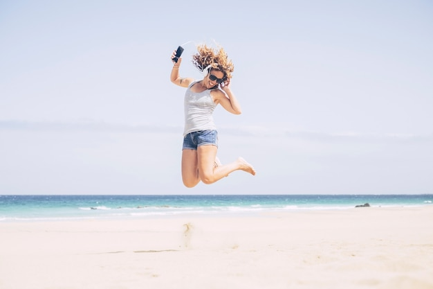 Cheerful and attractive caucasian young woman enjoy the beach and the summer vacation. listening music with phone and earphones jumping on the sand. holiday and happiness concept for free lady