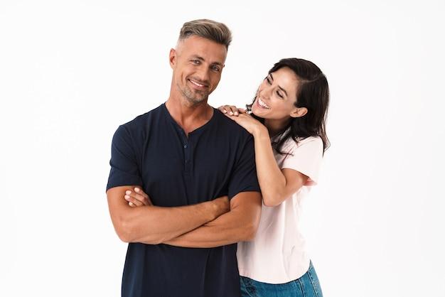 白い壁の上に孤立して立って、抱きしめてカジュアルな服を着て恋に陽気な魅力的なカップル