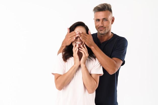 白い壁の上に孤立して立っているカジュアルな服を着て恋に陽気な魅力的なカップル、男性は女性の目を覆います