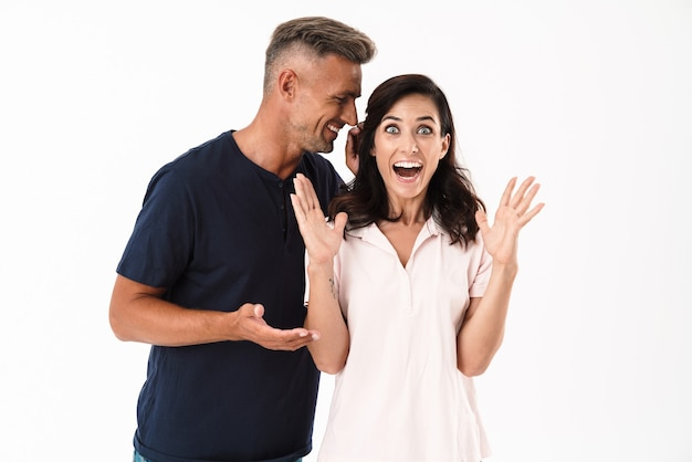 白い壁の上に孤立して立っているカジュアルな服を着て恋に陽気な魅力的なカップル、噂を語る男