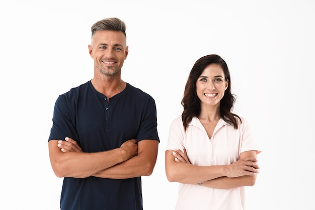 Веселая привлекательная пара в повседневной одежде, стоящая изолированно над белой стеной, скрестив руки на груди