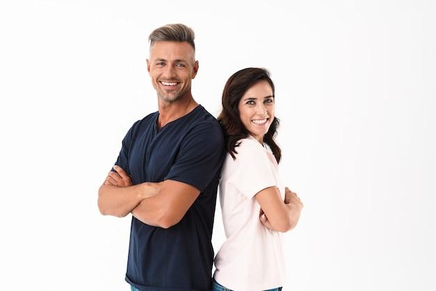白い壁の上に孤立して立っているカジュアルな服を着て、腕を組んで陽気な魅力的なカップル