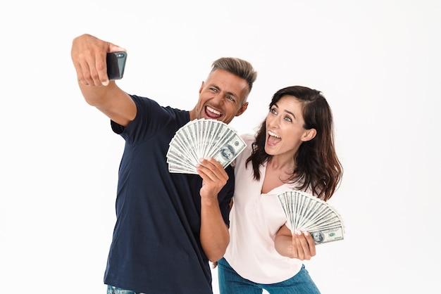 白い壁の上に孤立して立っているカジュアルな服を着て、お金の紙幣を保持し、自分撮りをしながら成功を祝う陽気な魅力的なカップル