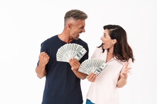 白い壁の上に孤立して立っているカジュアルな服を着て、お金の紙幣を保持しながら成功を祝う陽気な魅力的なカップル
