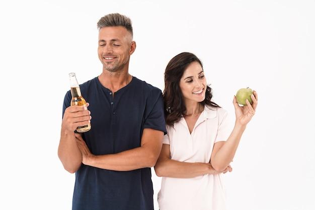 白い壁の上に孤立して立っているカジュアルな服を着て陽気な魅力的なカップル、ビール瓶を持っている男性、青リンゴを持っている女性