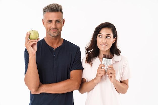 白い壁の上に孤立して立っているカジュアルな服を着ている陽気な魅力的なカップル、リンゴを持っている男性、チョコレートバーを持っている女性