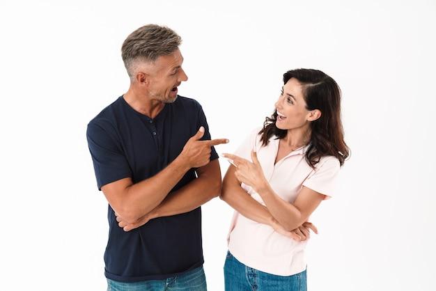 白い壁の上に孤立して立っているカジュアルな服を着て、お互いを指して、陽気な魅力的なカップル