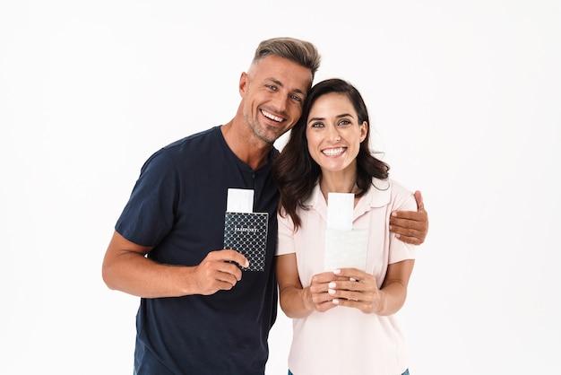 白い壁の上に孤立して立っているカジュアルな服を着て、航空券とパスポートを示す陽気な魅力的なカップル